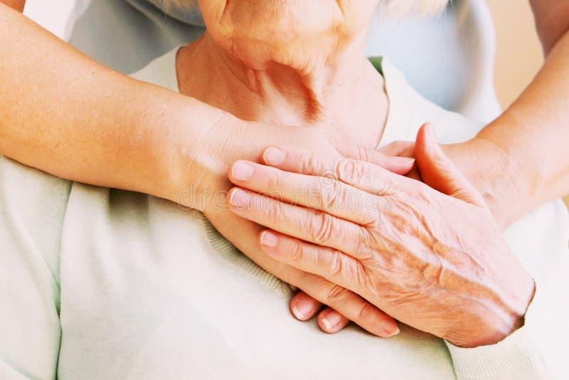 A fêmea madura em instalações de cuidados idosas obtém a ajuda da enfermeira dos pessoais do hospital Feche acima das mãos enruga fotografia de stock