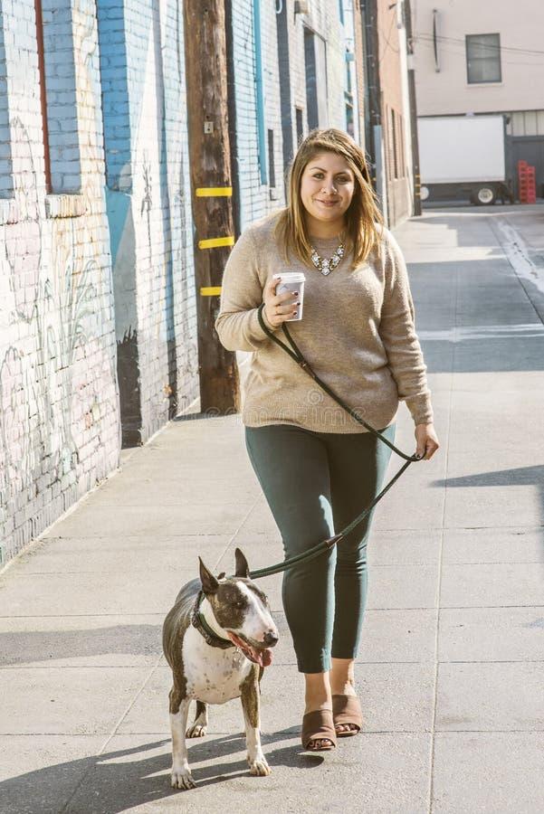 A fêmea milenar à moda anca nova anda seu animal de estimação bull terrier ao guardar um copo de Cofffee em uma aleia foto de stock royalty free