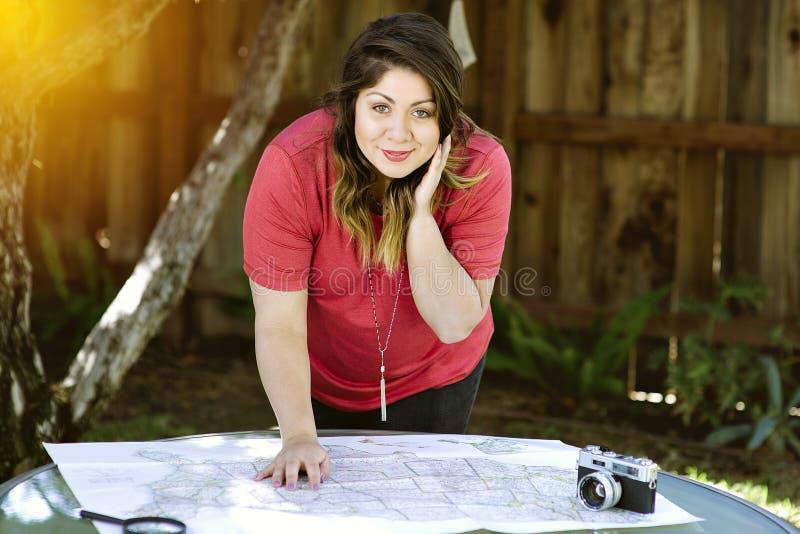 A fêmea milenar nova planeia seus cursos da viagem por estrada em um mapa com uma câmera fotos de stock royalty free