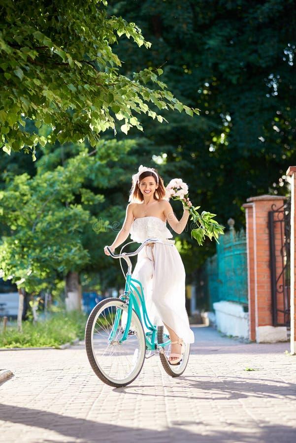 A fêmea monta a bicicleta do vintage com as peônias no fundo dos verdes foto de stock royalty free