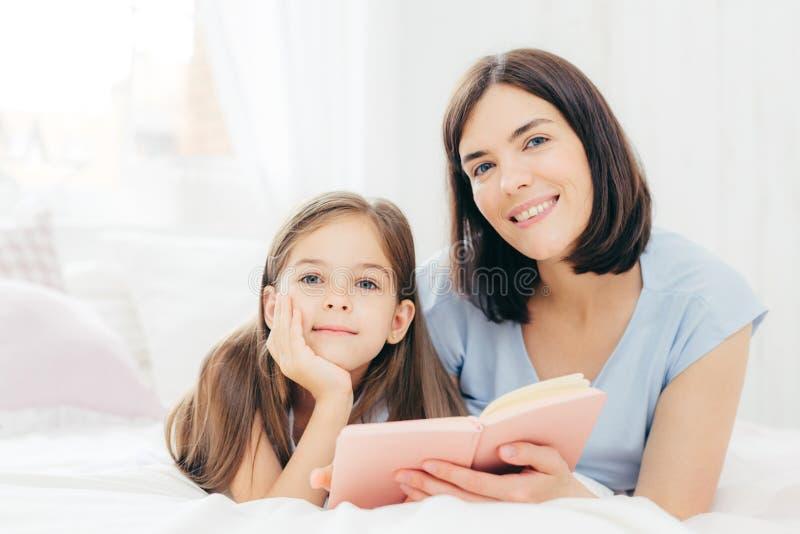 A fêmea moreno bonita com expressão alegre passa o tempo de lazer com sua filha, lê histórias interessantes para crianças, imagem de stock