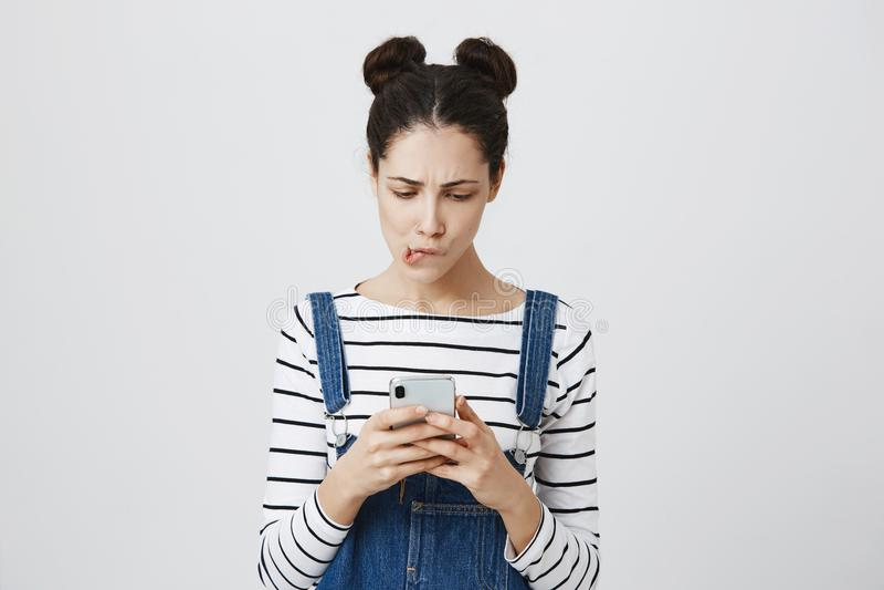 A fêmea moreno chocada com hairbuns guarda o telefone celular, chamada importante faltada, sendo confundido Mordidas horrorizadas fotografia de stock