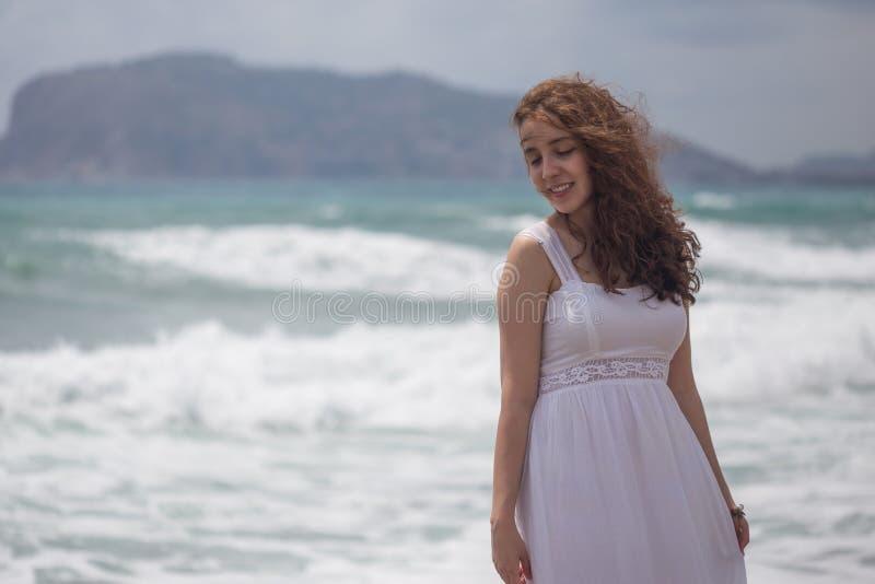 Fêmea moreno nova com o vestido branco vestindo do cabelo ondulado fotografia de stock
