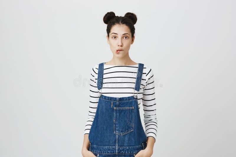 Fêmea moreno pensativa confundida com os dois hairbuns que vestem o macacão da sarja de Nimes que guarda as mãos em uns bolsos, m imagem de stock