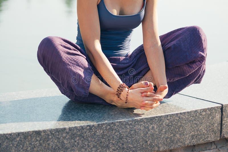 Fêmea na posição da ioga dos lótus exterior imagem de stock