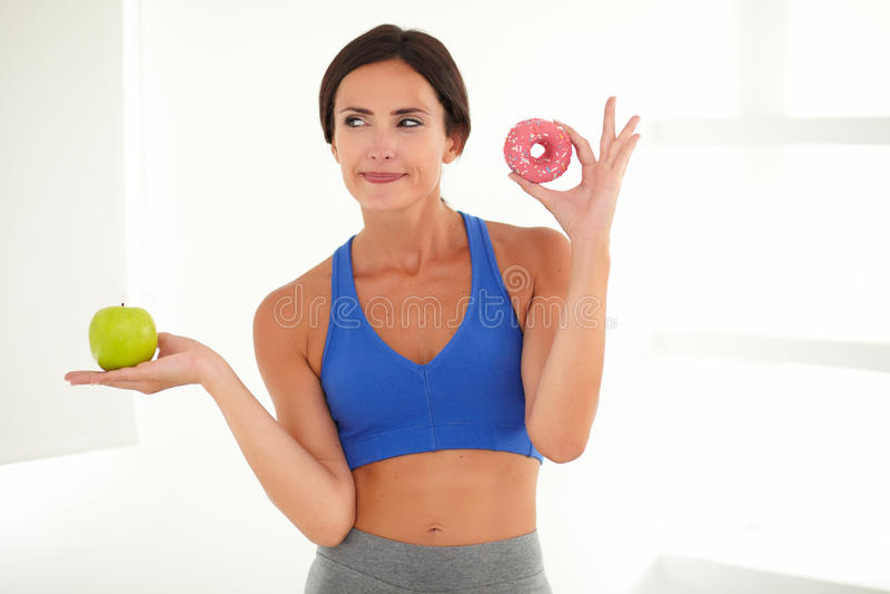 Fêmea na roupa do treinamento que guarda o alimento fotografia de stock royalty free