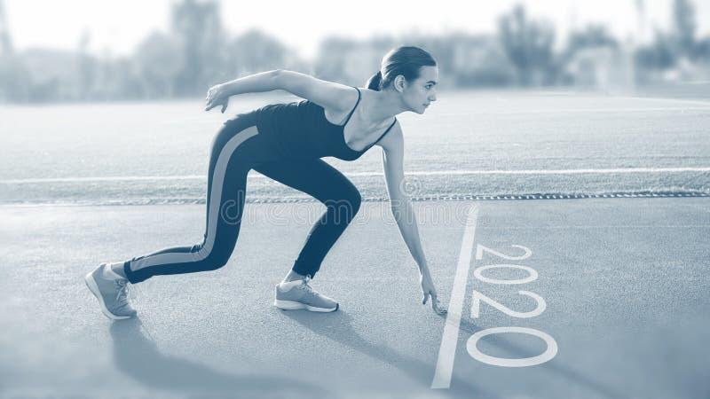 Fêmea no começo na pista de atletismo, sessão da linha de partida do exercício com texto 2020 imagens de stock