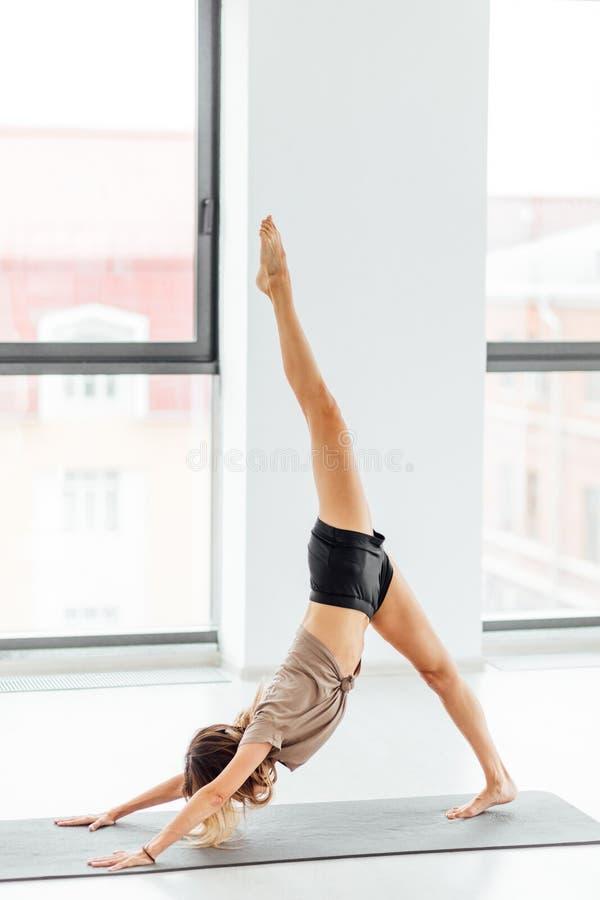 Fêmea no sportswear que está em um pé e que vai fazer uma postura do caranguejo fotos de stock royalty free
