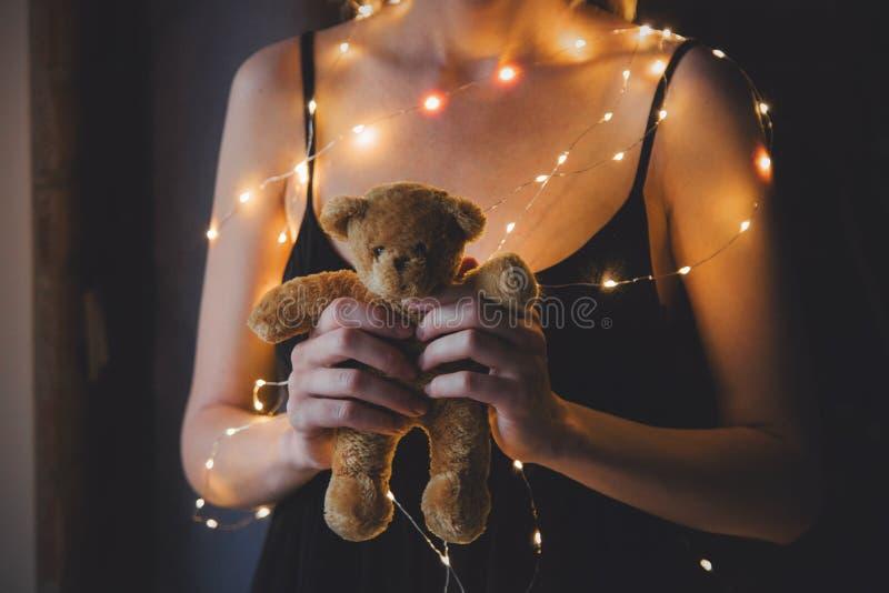 A fêmea no vestido preto e as luzes que guardam o urso de peluche brincam imagem de stock royalty free