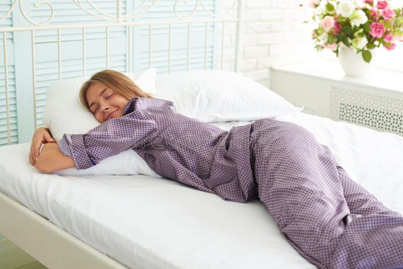 Fêmea nova atrativa em pijamas do cetim que dorme na cama com wh imagens de stock royalty free