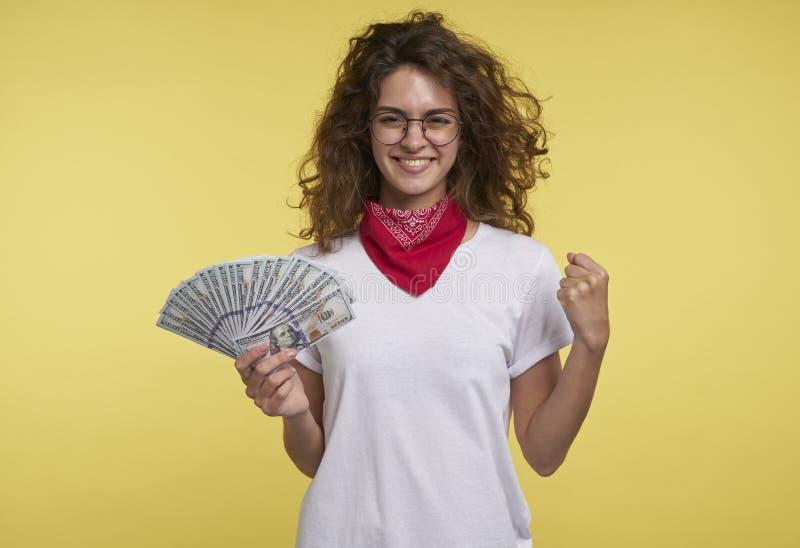 A fêmea nova bonita guarda o dinheiro na mão e mostra sim o sinal pela mão, sobre o fundo amarelo fotografia de stock royalty free