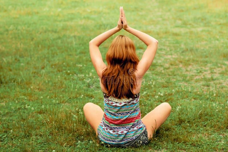 A fêmea nova bonita relaxa na pose da ioga na natureza verde Mulher da beleza que faz a ioga Conceito saud?vel e da ioga fotografia de stock