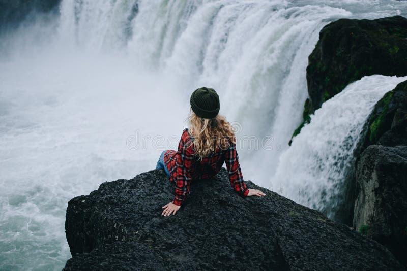 A fêmea nova bonita senta-se na borda do penhasco Islândia foto de stock royalty free