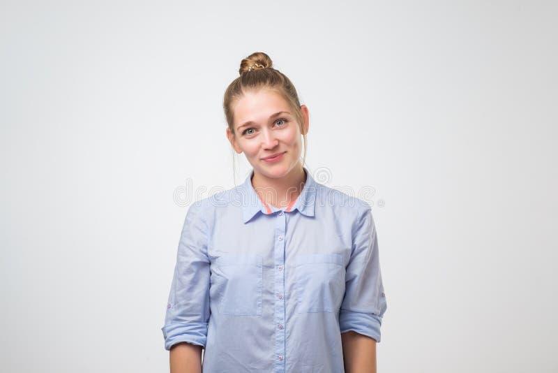 Fêmea nova bonito com o cabelo amarrado no nó que veste a camisa azul que tem a expressão feliz foto de stock royalty free