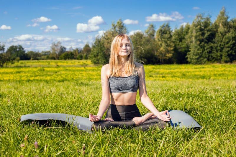 A fêmea nova com braços abertos e cabelo louro longo relaxa na pose da ioga na natureza verde imagens de stock