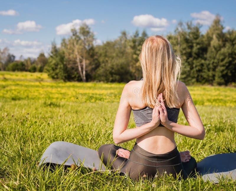 A fêmea nova com braços abertos e o cabelo louro longo que sentam-se para trás e relaxa na pose da ioga na natureza verde imagem de stock royalty free