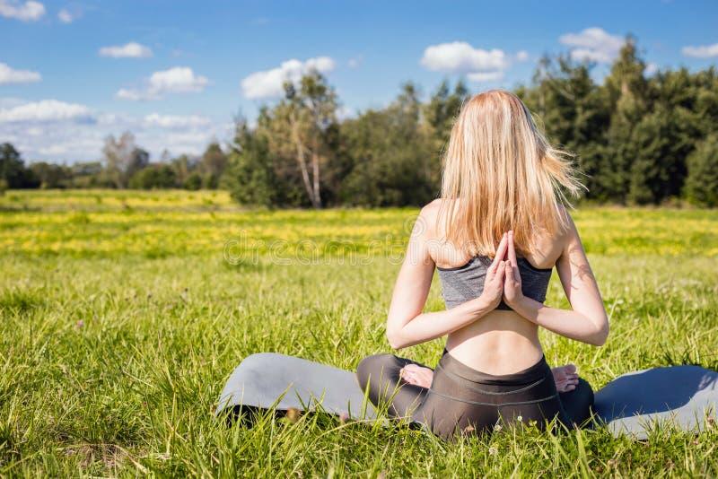 A fêmea nova com braços abertos e o cabelo louro longo que sentam-se para trás e relaxa na pose da ioga na natureza verde imagem de stock