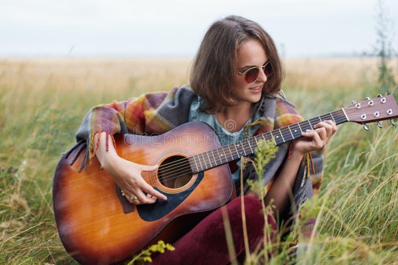 Fêmea nova com o cabelo curto escuro que senta-se na grama verde que joga fora a guitarra que aprecia paisagens agradáveis que ca fotos de stock royalty free