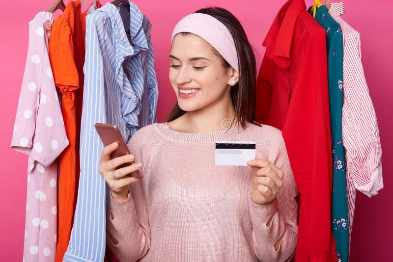 A fêmea nova de cabelo escura bonita com expressão alegre, guarda o cartão esperto do telefone e de crédito A menina feliz faz o  imagem de stock