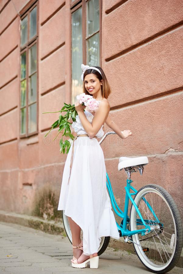 Fêmea nova de sorriso no vestido branco que levanta com as peônias perto da bicicleta azul na frente da construção histórica verm fotos de stock