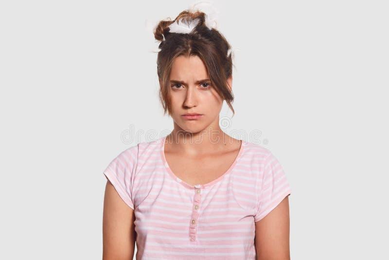 A fêmea nova desagradada sombrio tem a expressão solene, tem o humor mau cedo na manhã como quer para dormir, vestido no equipame imagem de stock