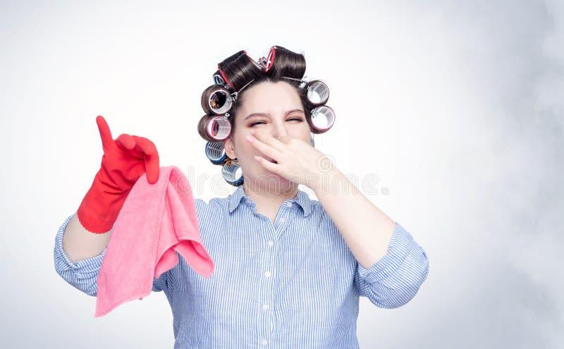A fêmea nova em encrespadores de cabelo comprime emocionalmente seu nariz com uma mão do fedor foto de stock royalty free