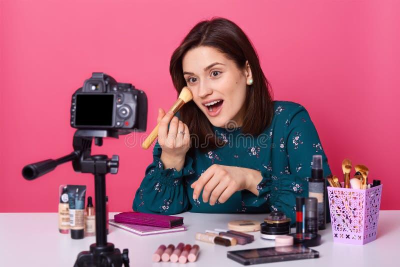 A fêmea nova engraçada emocional senta-se na tabela com cosméticos, disparar novo compõe o curso para seu blogue, abrindo a boca  fotografia de stock