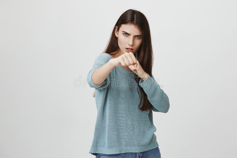 Fêmea nova europeia à moda feroz e segura na camiseta fraca azul com o cabelo escuro longo que guarda os punhos na frente de imagens de stock royalty free