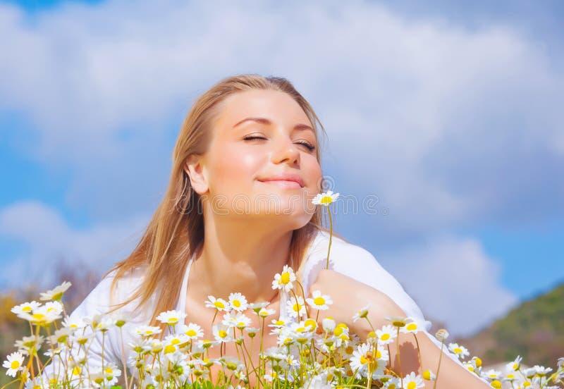Mulher bonita que aprecia o campo da margarida e o céu azul imagem de stock royalty free
