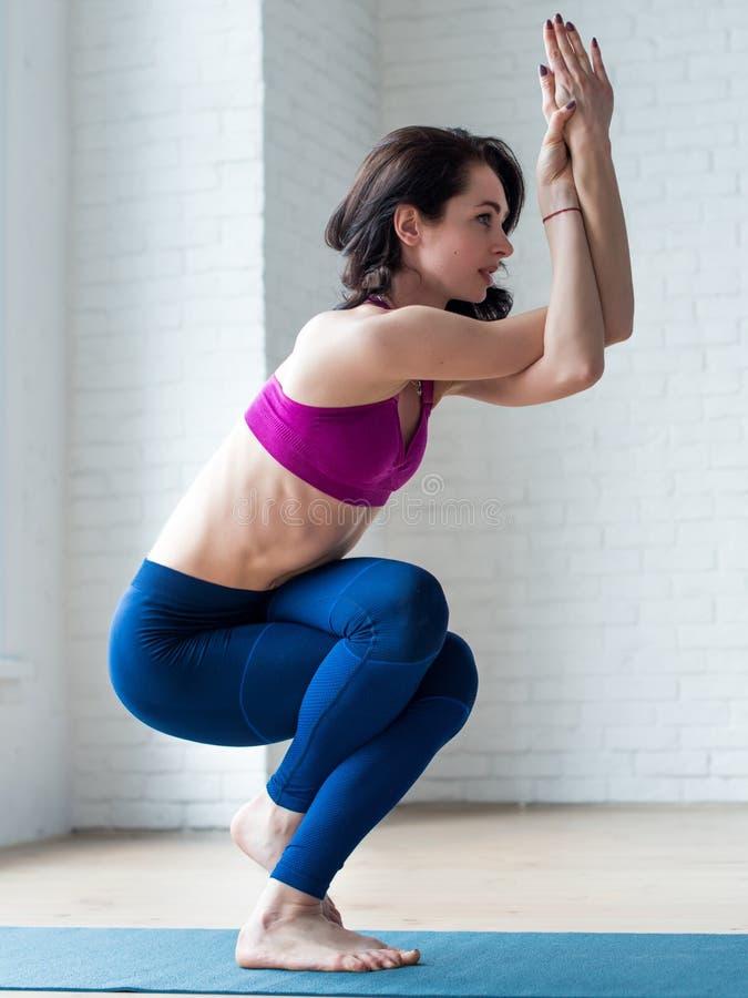 Fêmea nova magro no sportswear que faz a pose de Eagle, Garudasana, no gym imagens de stock royalty free