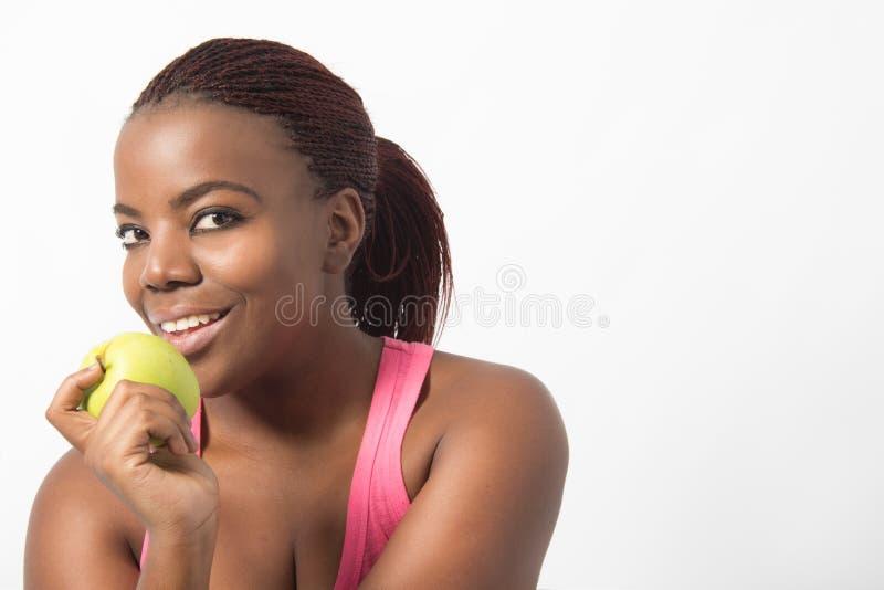 Fêmea nova preta que guarda uma maçã verde fotos de stock