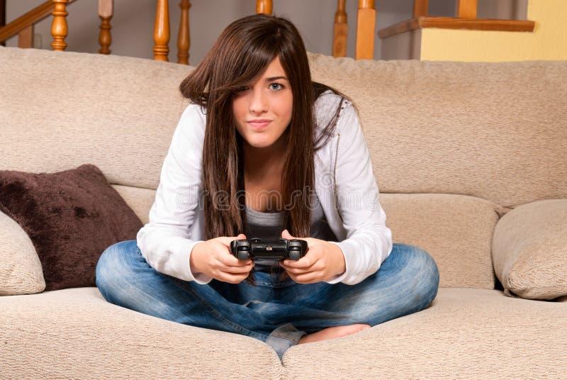 Fêmea nova que concentra-se jogando videogames imagem de stock royalty free