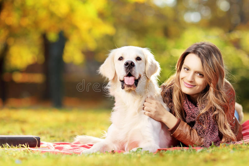 Fêmea nova que encontra-se para baixo com seu cão em um parque foto de stock