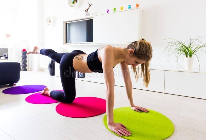 Fêmea nova que faz seu exercício do aumento do pé em sua casa foto de stock