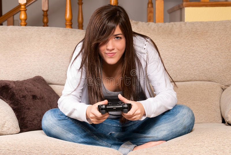 Fêmea nova que joga os videogames que concentram-se no sofá em casa imagens de stock royalty free