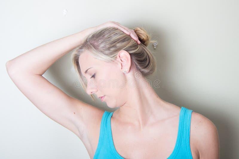 Fêmea nova que usa exercícios de pescoço das mãos fotografia de stock royalty free