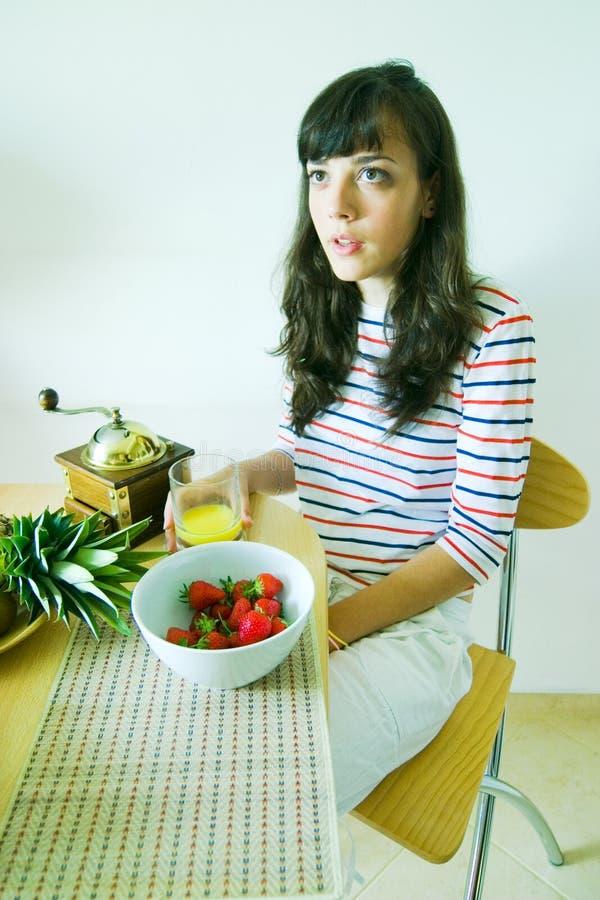 Fêmea novo comendo o pequeno almoço foto de stock