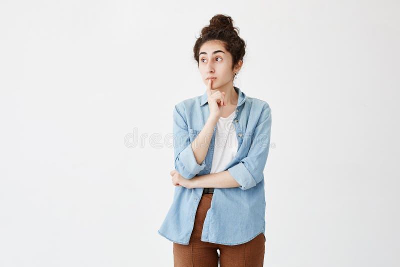 A fêmea pensativa com bolo do cabelo, mantém o dedo nos bordos, olha com expressão pensativa de lado, na camisa da sarja de Nimes fotografia de stock royalty free