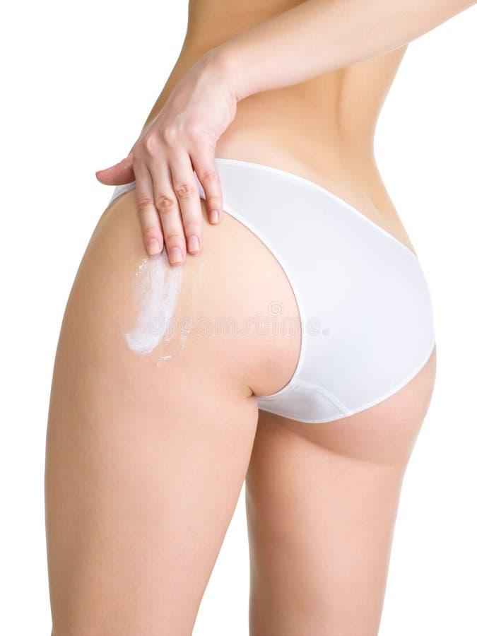Fêmea que aplica o creme cosmético no pé fotos de stock