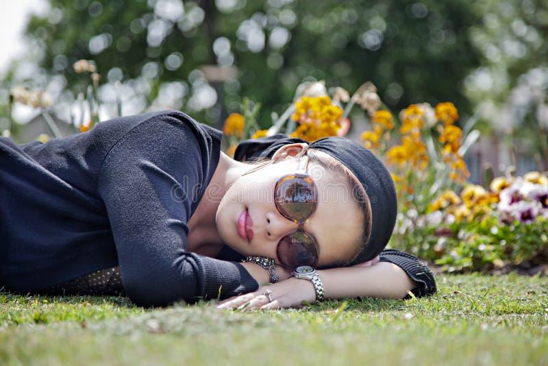 Fêmea que coloca na grama fotografia de stock