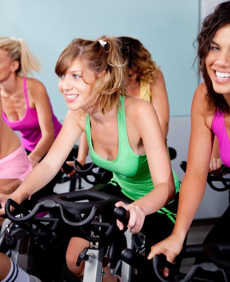 Fêmea que dá um ciclo no clube de aptidão imagens de stock royalty free