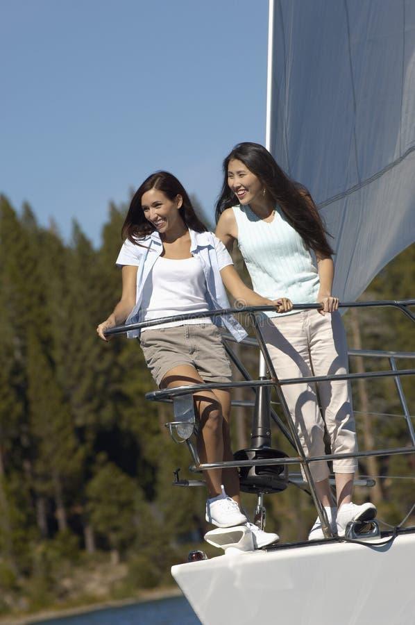 Fêmea que está junto no veleiro foto de stock royalty free
