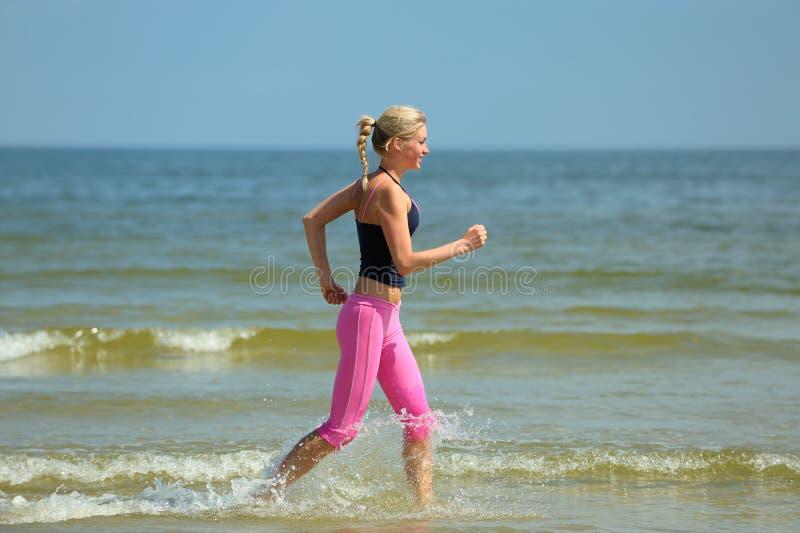 Fêmea que funciona na praia fotos de stock