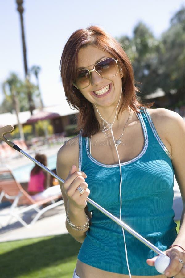 Fêmea que guardara um clube e uma bola de golfe fotos de stock