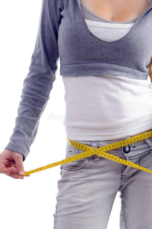 Fêmea que mede sua cintura com fita imagem de stock royalty free