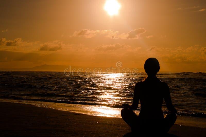 Fêmea que meditating na praia fotografia de stock