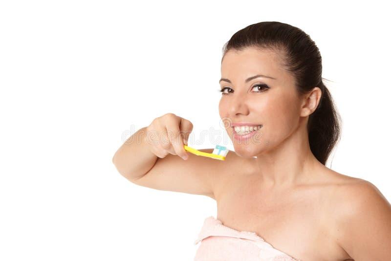 Fêmea que prende um toothbrush com dentífrico foto de stock