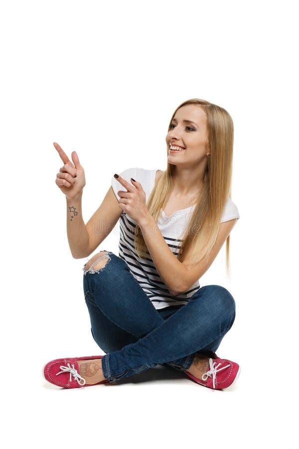 Fêmea que senta-se com pés cruzados no assoalho que aponta ao lado imagens de stock