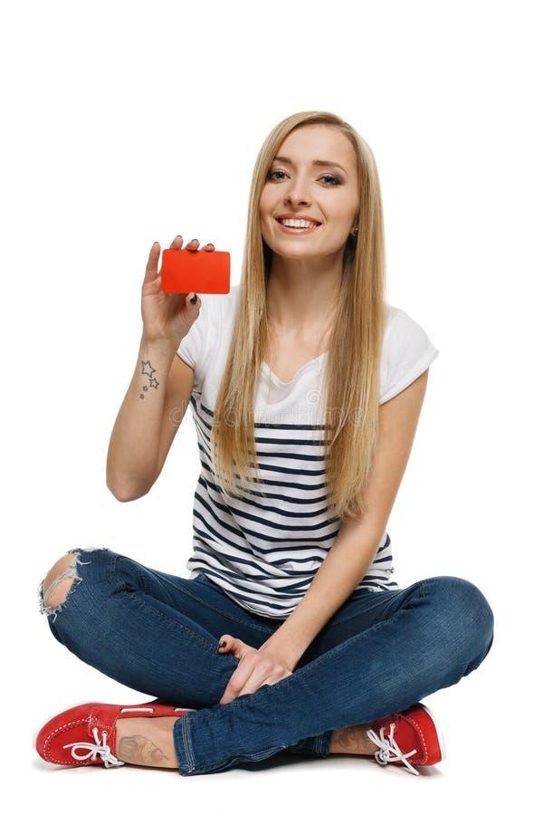 Fêmea que senta-se no assoalho e que mostra o cartão de crédito vazio fotos de stock