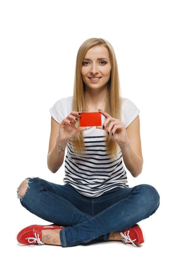 Fêmea que senta-se no assoalho e que mostra o cartão de crédito vazio imagens de stock